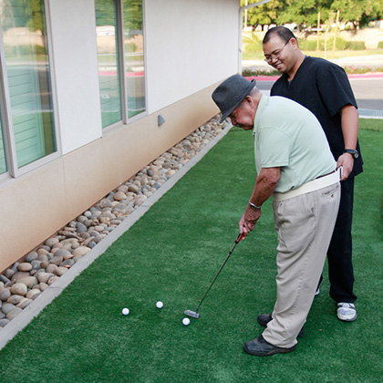 two men playing golf on a putting green outside