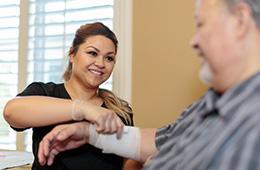 nurse bandaging a resident's arm