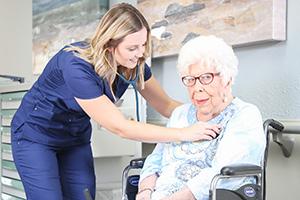 nurse buttoning resident's jacket