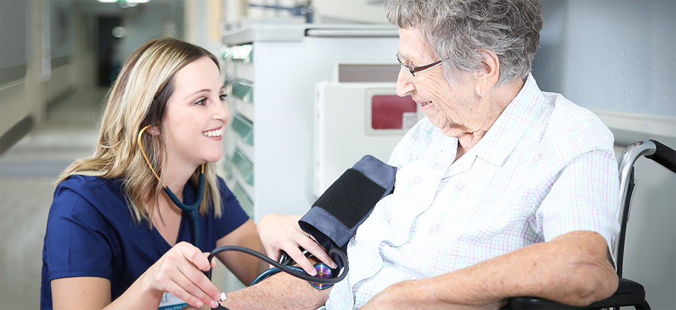 nurse taking a resident's blood pressure