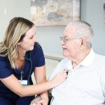 nurse listening to resident's heart beat