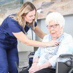 nurse listening to female resident's heart beat