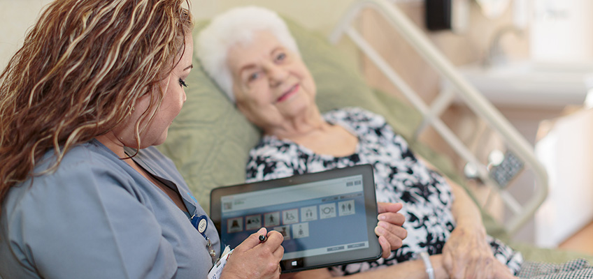 nurse using a tablet and a smiling elderly woman laying down
