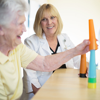elder woman doing physical therapy by stacking thin tall tubes