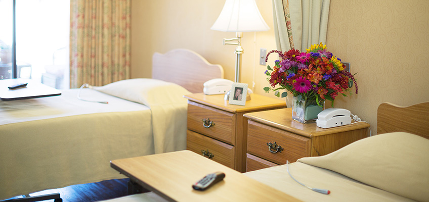 two beds with bedside tables and phones and a television remote on each bed-table