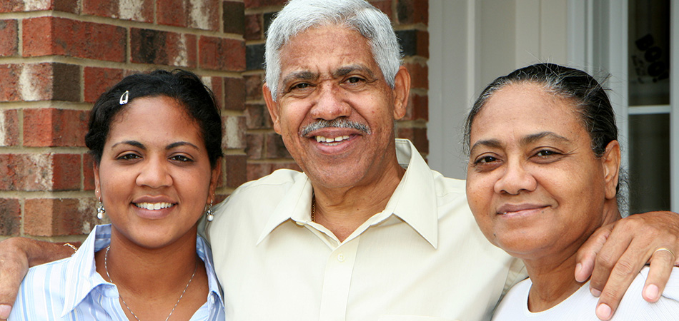 smiling family standing outside in front of a brick wall