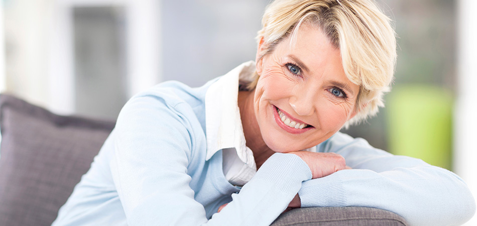 smiling mature woman with short blonde hair and a light blue sweater