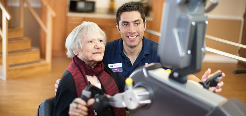 resident using hand bike with therapist