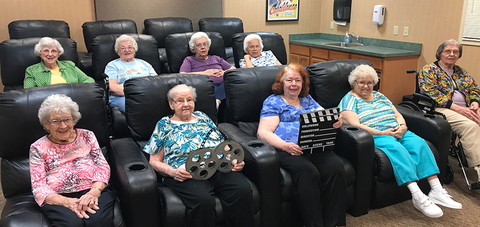 Residents sitting together in big movie lounging seats about to watch a movie at the facility