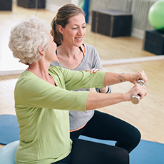 Rehabilitation staff assisting a resident with lifting dumbbells