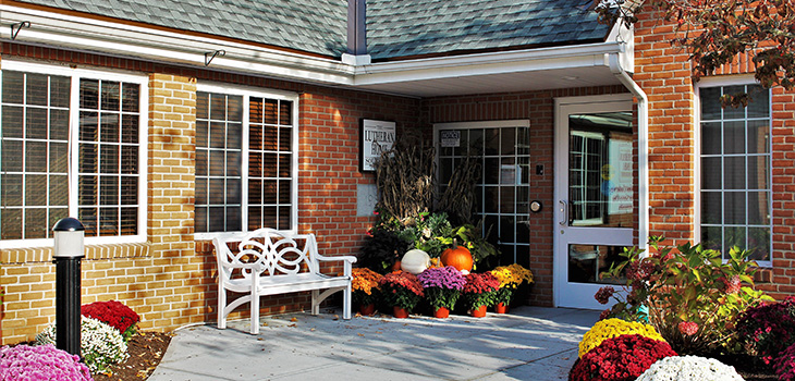 Nursing Home Southbury front door entrance with flowers and park bench seating.