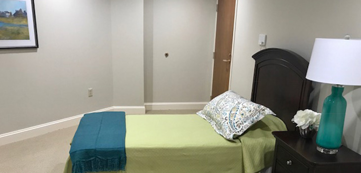 Nursing Home Southbury bedroom with a nightstand and a lamp.