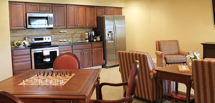 Nursing Home Southbury activity room and occupational therapy room with a chess board, kitchen, and seating.