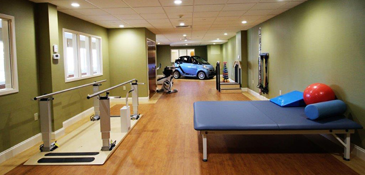 Nursing Home Southbury rehabilitation gym neatly organized including equipment and a car for practice.
