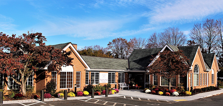 Nursing Home Southbury outdoor entrance with lush flowers lining the walking path and handicap parking.