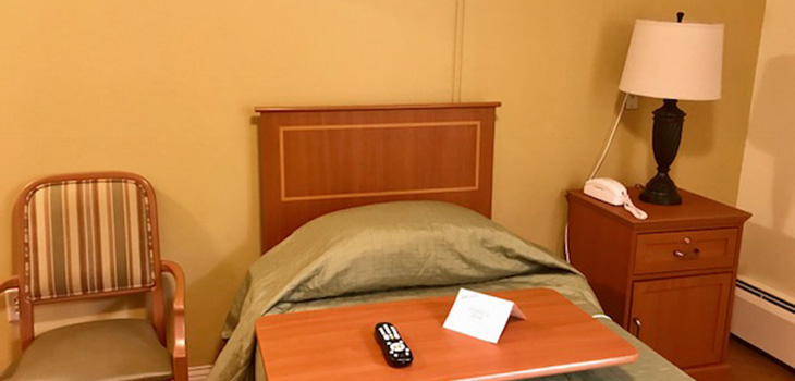 Nursing Home Southbury bedroom, nightstand, seating, remote control, and phone.