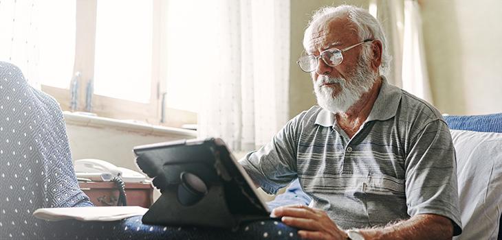 elderly man looking at an ipad