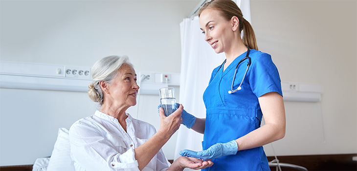 nurse giving a patient water and medicine
