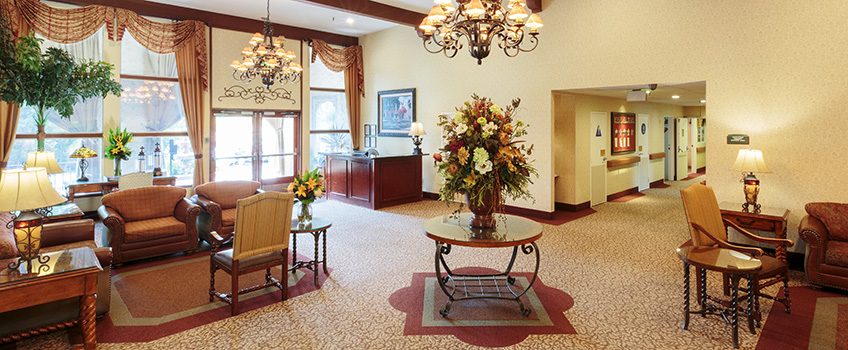 comfortable lobby with chandeliers, flower centerpieces and large draped curtains