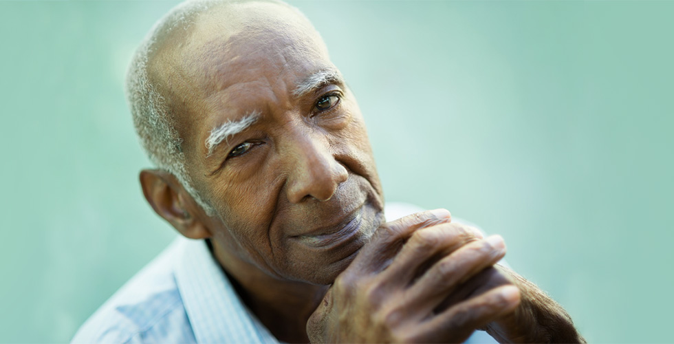 elderly man smiling with hands folded