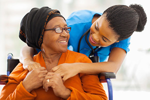 nurse leaning down to help a resident button her sweater