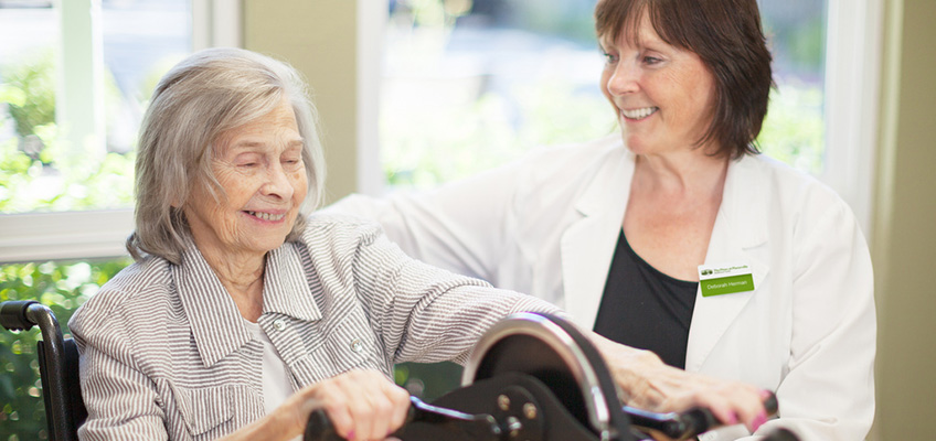 resident using hand bike with smiling nurse