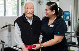 smiling nurse assisting a patient on the parallel walking therapy bars