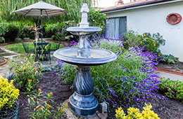 outdoor fountain with pretty plants and outdoor seating