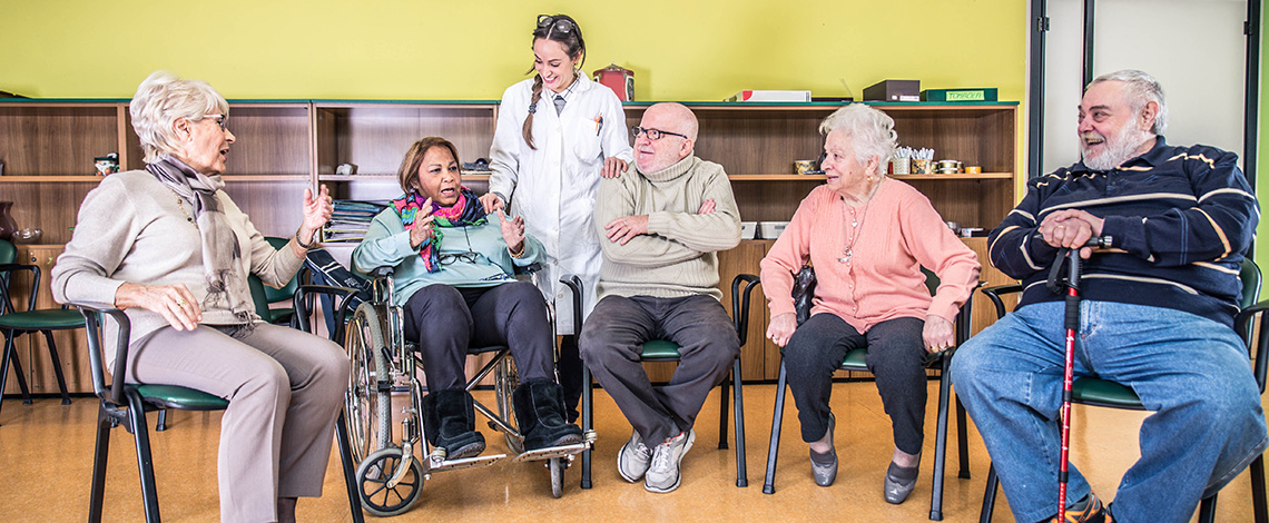 Residents sitting in a half circle with a staff member talking and laughing in a room.