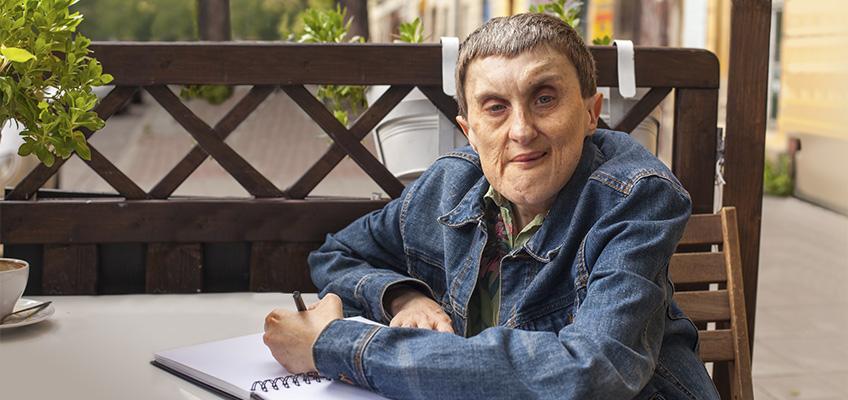 TKJ resident sitting outside writing in a journal