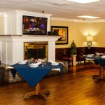 Capistrano Care Center dining room with a huge fireplace and flat screen TV above