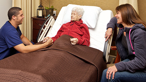 woman in a hospital bed speaking with medical staff & family member