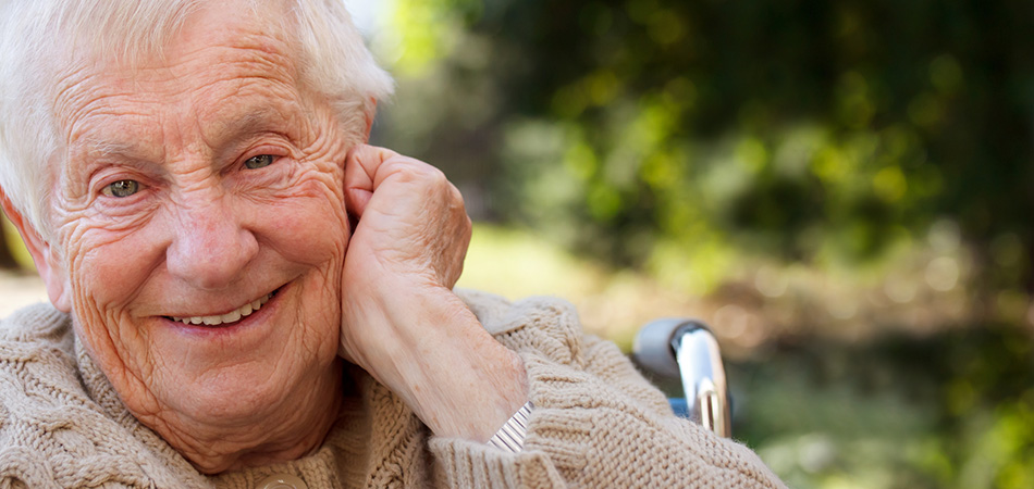 An elderly man sitting in a wheelchair smiling