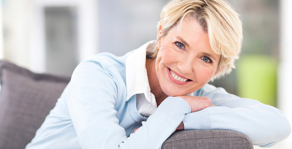 Woman with her arms folded on a couch in front of her