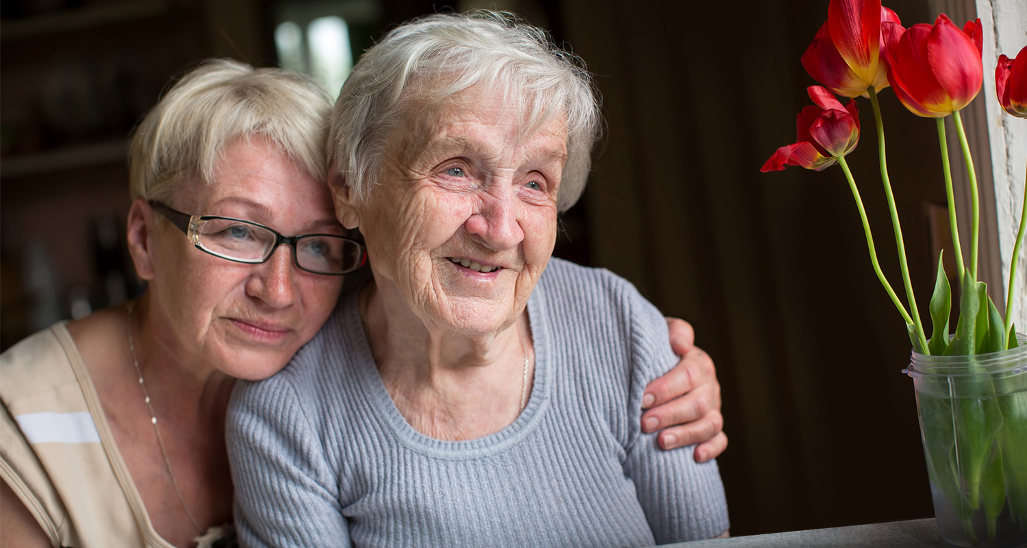 middle aged woman with her arm around an elderly woman while both look out the window