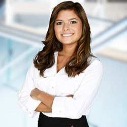 standing female professional smiling with her arms crossed