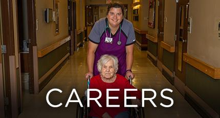 nurse happily pushing resident down the hallway
