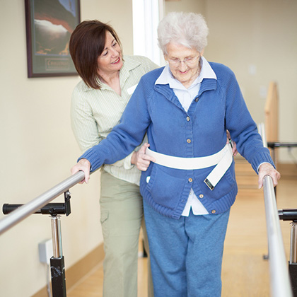 woman using parallel bars for physical therapy