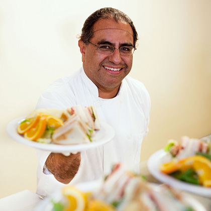 chef serving club sandwiches and oranges
