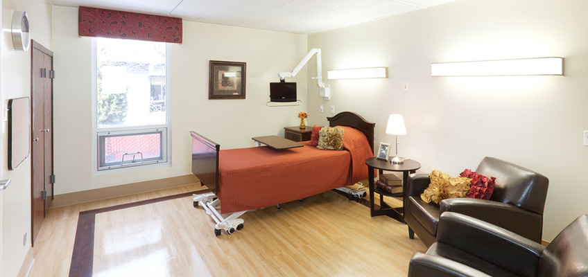one bed room with television, bed and chairs to sit in