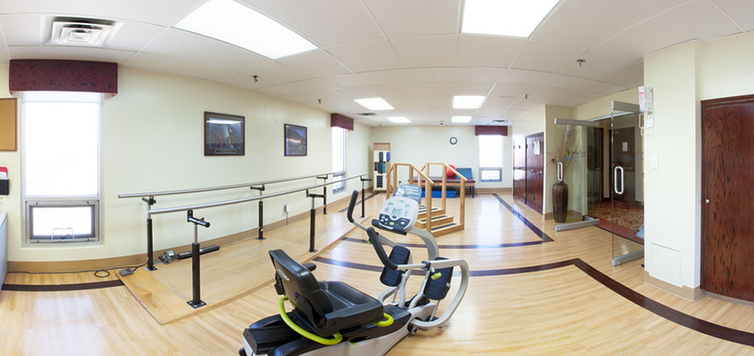rehabilitation area with wooden floor and various equipment