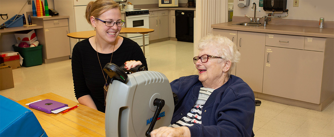 A nurse helping a resident improve her strength in the fitness room