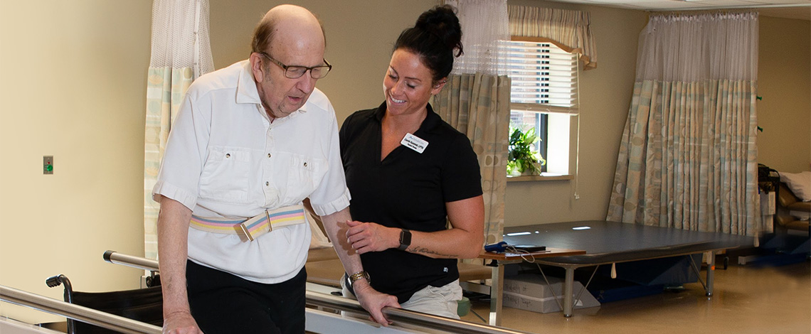 A nurse helping a resident walk in the fitness room