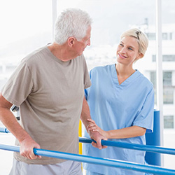 male resident working on parallel walking bars with a therapist