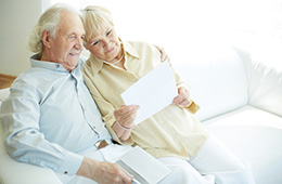elderly couple reading a greeting from a loved one