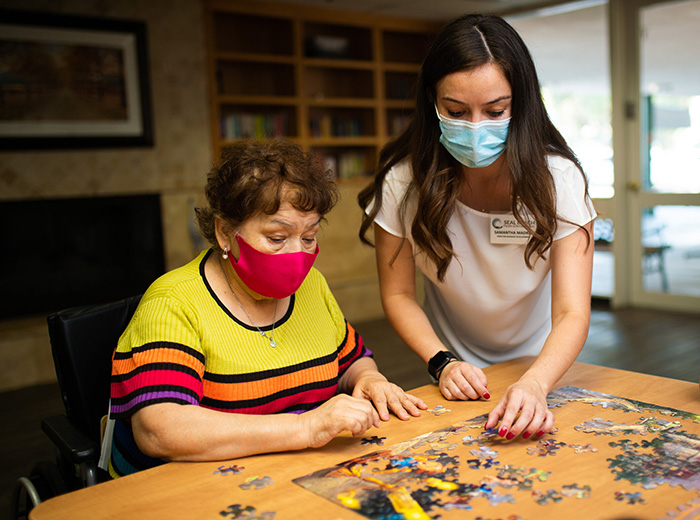 residents and nurse putting a puzzle together