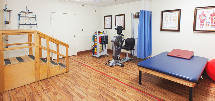rehabilitation room with wood flooring and different styles of equipment