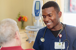 smiling nurse with stethoscope and helping a patient