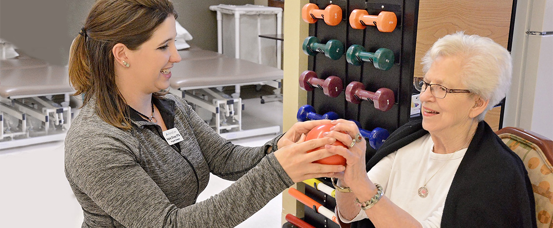 A nurse helping with a woman's strength exercises