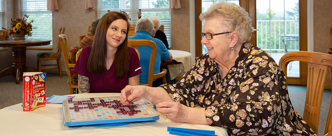 An employee playing scrabble with a kind resident